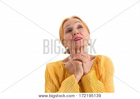 Sad woman with folded hands. Senior female on white background. Wish for better times.