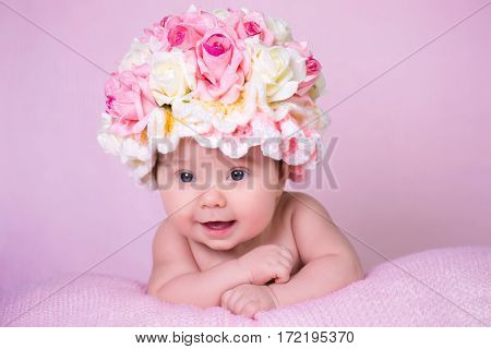 A newborn baby girl in the hat of the rose smiles. Portrait on a pink background
