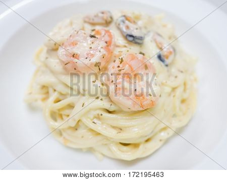 Pasta Carbonara with seafood on a white plate