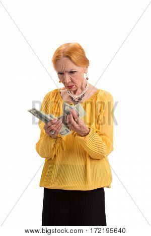 Senior woman holding money isolated. Serious lady looking at cash. Choose best pension fund.