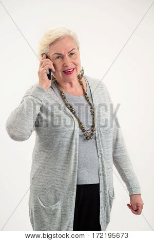 Old lady holding cell phone. Elderly woman isolated. Best prices for international calls.
