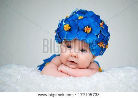 Newborn girl in a cap of blue flowers primrose.