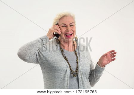 Smiling elderly woman with cellphone. Happy senior woman isolated. Affordable tariffs and stable connection.