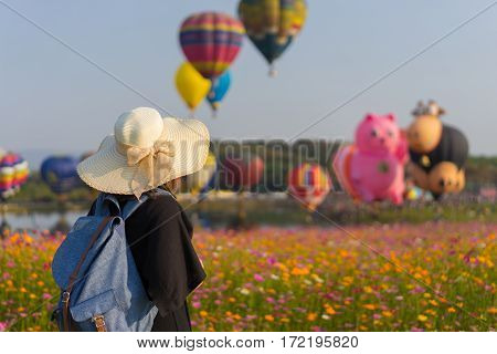 Woman tourist is traveling into Balloon festival in Chiangrai Provice Thailand. Woman traveller with white hat and bag standing looking beautiful balloon in cosmos flower field.