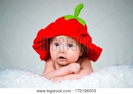 Beautiful baby girl in a knitted hat strawberry.