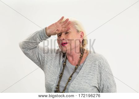 Senior woman touching her forehead. Tired lady on white background. Strong pulsing headache.