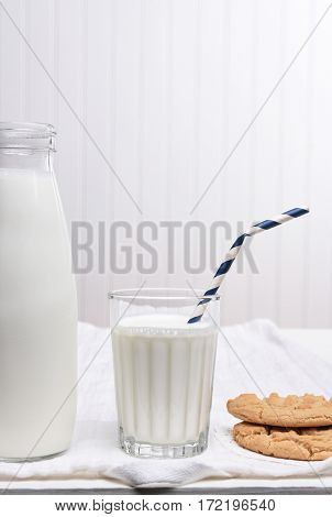 A Milk and Cookie Snack on a white table with white wall. The glass has a Drink Straw with cookies by its side.