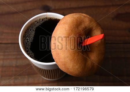 high angle view of a paper cup of hot fresh brewed coffee with a red spoon, A plain old fashioned donut is hanging on the spoon.