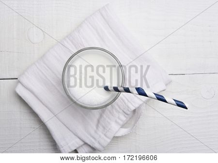High angle view of a glass of milk and a drinking straw.