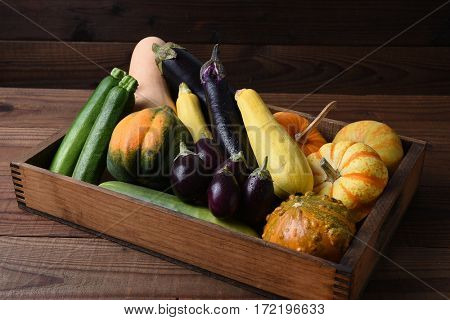 A wood box filled with various vegetables, squash and gourds.