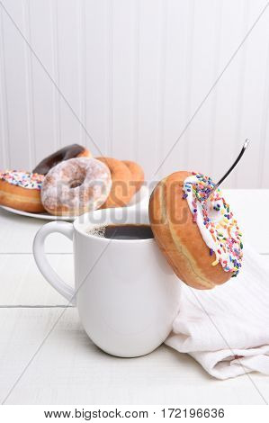 Closeup of a mug of hot coffee with a donut hanging off the spoon inside the cup. A plate of assorted donuts is in the background. Vertical with copy space.