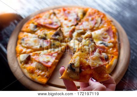 Fresh Pizza On A Wooden Plate In Female Hands. Selective Focus.