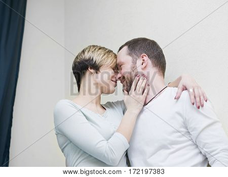 A couple wearing casual wear hugging cropped indoor portrait