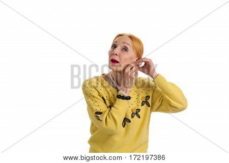 Woman fixing earrings. Senior lady isolated on white background.