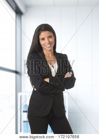 corporate portrait of young attractive latin business woman wearing formal suit smiling happy and confident posing at modern office next to the window in work success concept