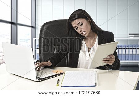 young busy beautiful latin business woman suffering stress working at office computer desk worried and desperate at work using digital tablet talking on mobile phone in overwork concept