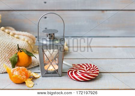 Christmas Still Life With Lantern, Plaid, Lollipop, Tangerine And Red Beads On Wooden Background