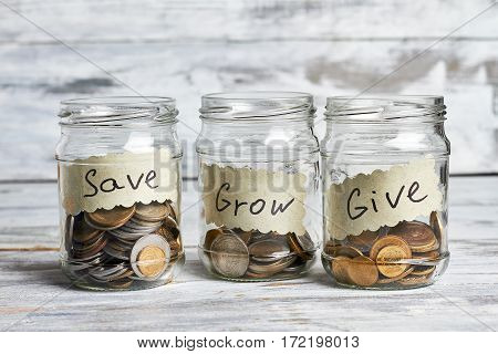 Three glass containers with coins. Idea of spending money.