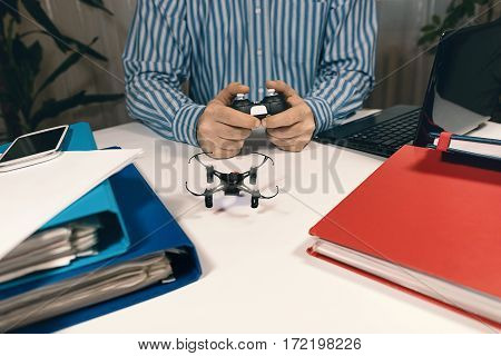 Businessman playing with drone toy to Relieve Stress at Work. Businessman testing new toy on desk in office.