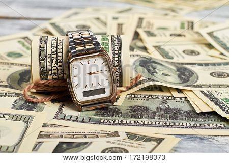 Wristwatch and dollars. Planning financial success. Old watch.