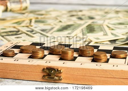 Coins on chessboard and dollars. Rate on money in business.