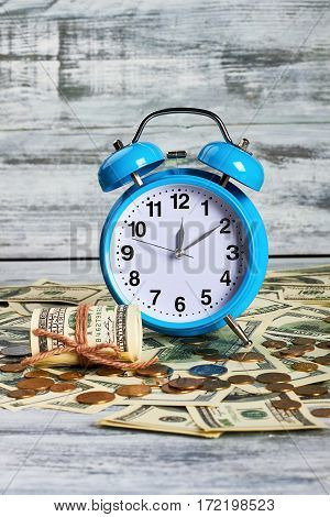 Alarm clock and american currency. Profitable working day.