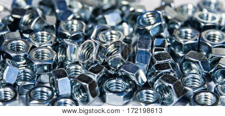 Close-up of stainless steel nuts, metal screw nuts, nuts made of chrome, nuts background, set of small and big iron nuts on white surface