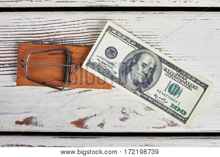 Mousetrap and dollars on wood. Money is trap for soul.