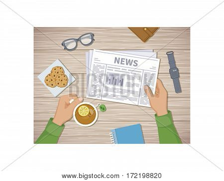 Man reading the latest news at breakfast. Human hands holding tea with lemon and newspaper, cookies, glasses, smart watch, notebook, purse. A good start of the day before working. View from above.