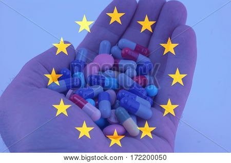 Hand holding multicolored pills European union flag background