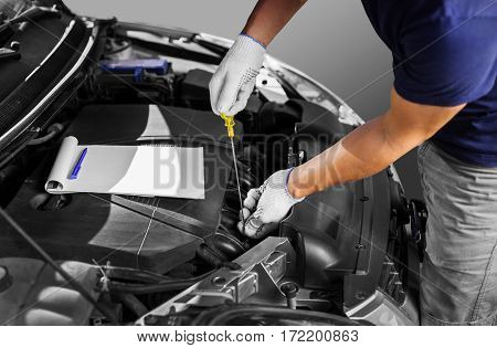 Auto mechanic checking the oil level in car engine.