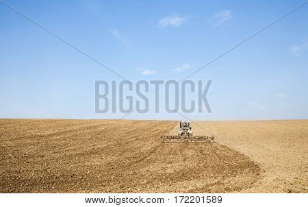 Harrowing the soil with tine harrows in spring in Ukraine.