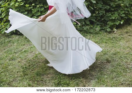 Bride in a stylish white dress dancing for a groom outside. Dress flying up in wind. Flowing fluttering dress. Happy woman on a walk on her wedding day. Beautiful sunny summer day.