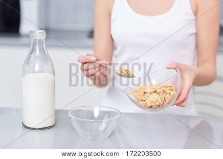 Crop of woman in white top cooking breakfast with oak flakes and milk, pouring at two plates. Incognito female preparing healthy food. Stylish interior of kitchen.at modern kitchen