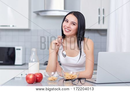 Attractive girl with long hair smiling at camera and holding spoon in hand. Woman in white top eating her breakfast of oak flakes and milk. Near on table laptop, eyeglasses and two big apples.