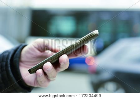 closeup of a young caucasian man using a smartphone in the street