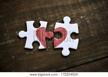 closeup of two separated pieces of a puzzle which together form a heart on a rustic wooden surface, depicting the idea of rupture or cooperation