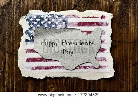 the flag of the United States in an aged piece of paper and the text happy presidents day written in a piece of paper in the shape of the United States, on a rustic wooden background