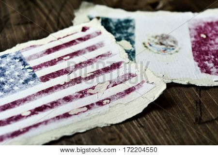 the flag of United States and the flag of Mexico in two aged pieces of paper on a rustic wooden background