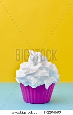 closeup of a pink plastic cup full of a white ice cream on a blue and yellow background