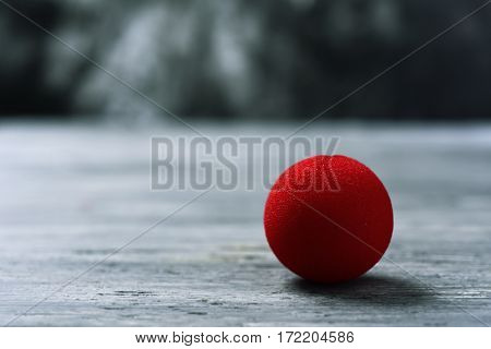 a red clown nose on a rustic wooden surface