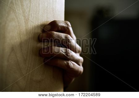 closeup of the hand of a young caucasian man popping out strongly from behind a door