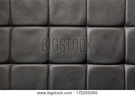 A pattern of black leather tiles stitched together