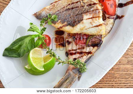 Fried Fish Dorado Garnished on Sliced Pumpkin with Basil Leaf and Sauce