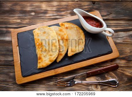 Tasty Pasties  Filled With Meat And Vegetables On Board With Red Sause
