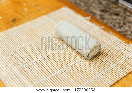 Preparing sushi ready for cutting on bamboo mat.