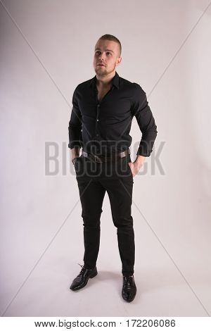 Serious Man Wearing Black Shirt And Black Pants Standing And Looking Forward. Full Length Studio Por