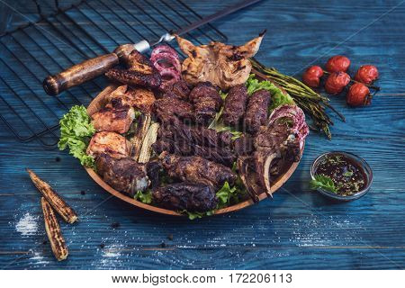 Grilled different meat with vegetable on a blue wooden background