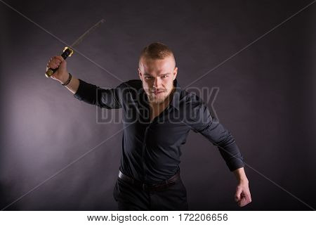 Aggressive Young Man Holding Katana Sword Looking At The Camera.against Wall Background