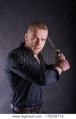 Man In Black Shirt Holding Katana Sword Looking At The Camera Against Wall Background